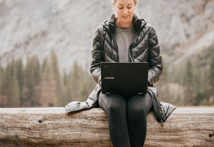 Woman wearing a black puffy jacket using her laptop outside